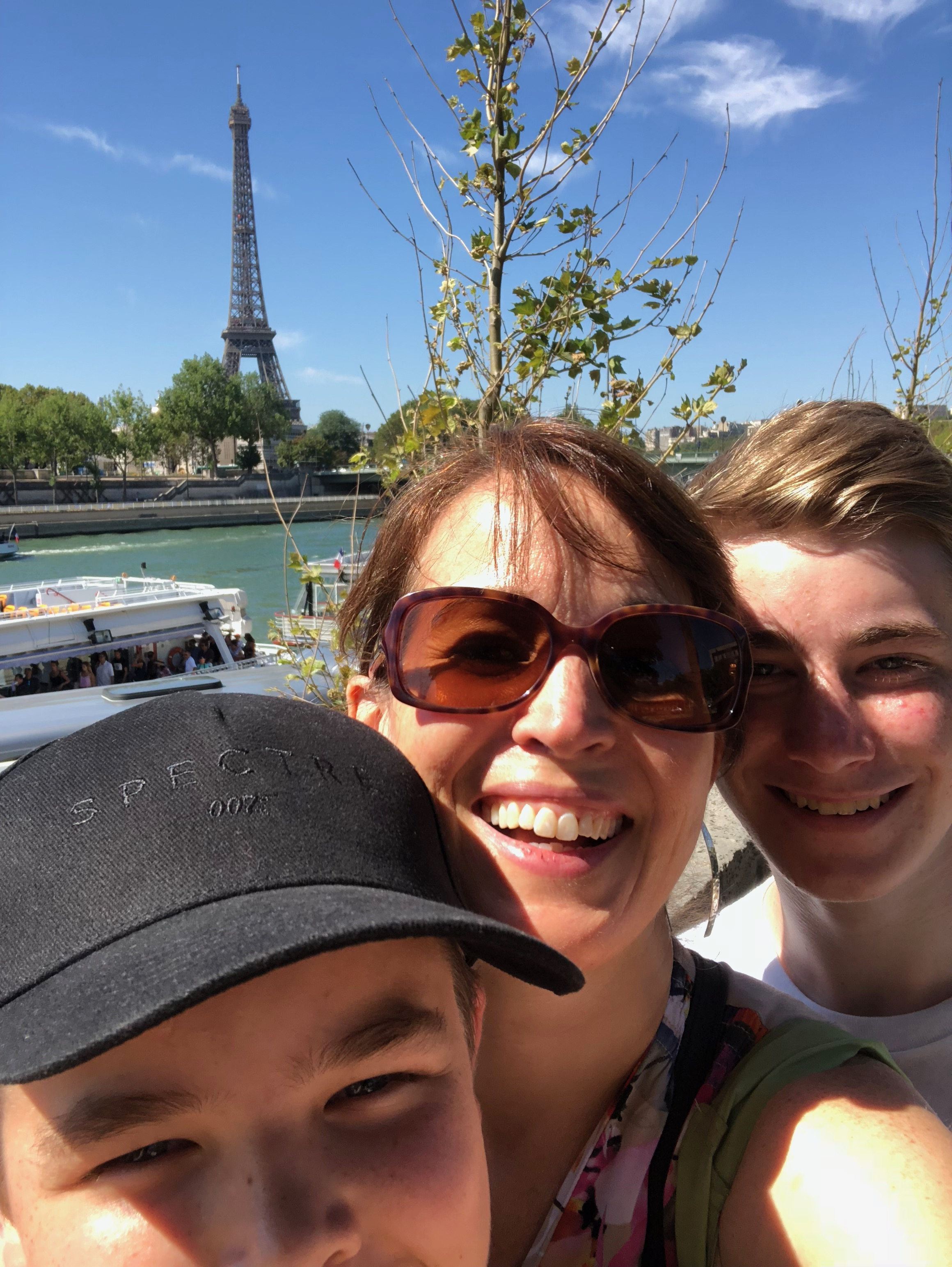 Kathy and her two sons take a group selfie with the Seine and Eiffel Tower over their shoulder
