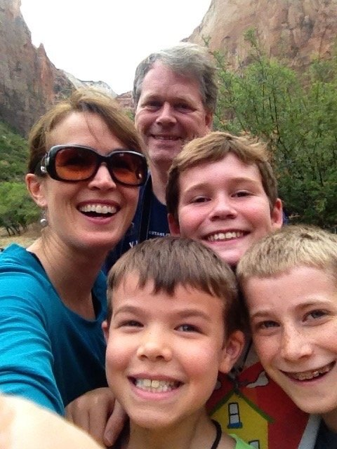 Happy family of five posing in front of the Three Sisters in Zion National Park