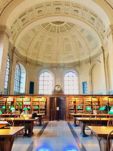 Boston Public Library's iconic main reading room, Bates Hall, has a soaring barrel-vaulted ceiling, table lamps with free shades, and wooden bookcases.
