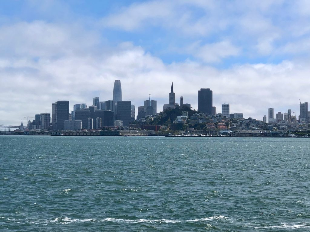 View of San Francisco taken from a bay cruise, showing the city's skyline under blue skies.