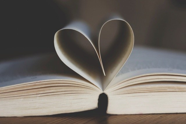 The pages of this book are curled together to form the shape of a heart, symbolizing the books we love for this list of the best books for travel lovers