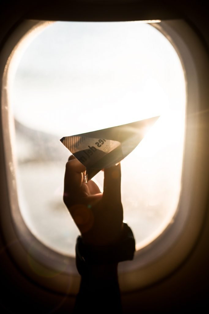 A backlit hand holds a paper airplane in front of an airplane window.