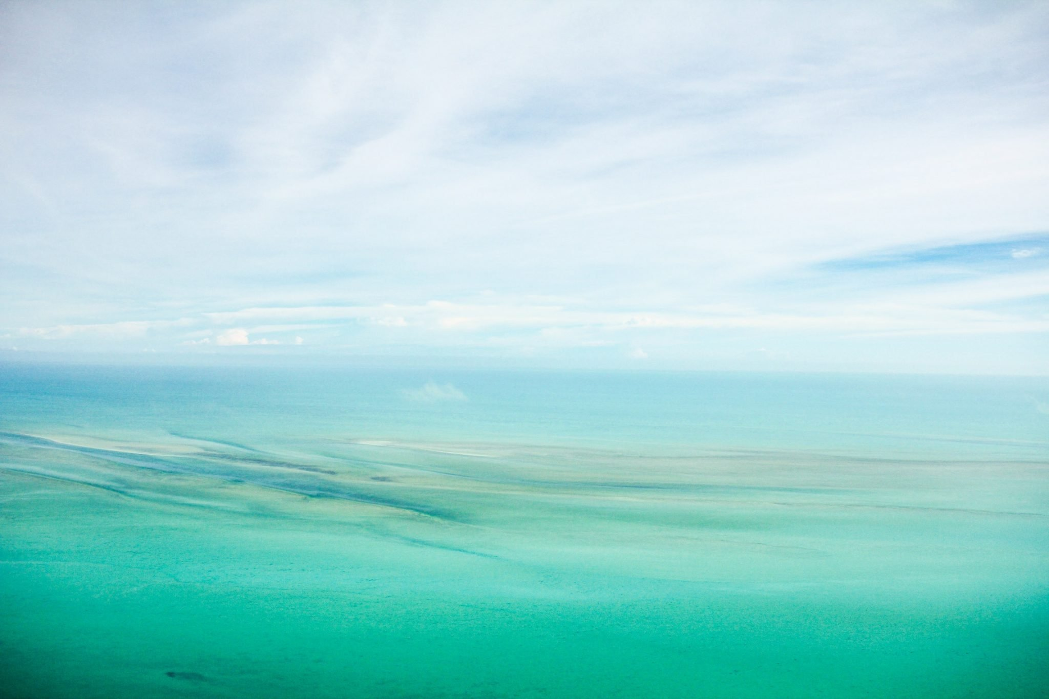 Turquoise waters of the Caribbean against a bue sky with puffy white clouds