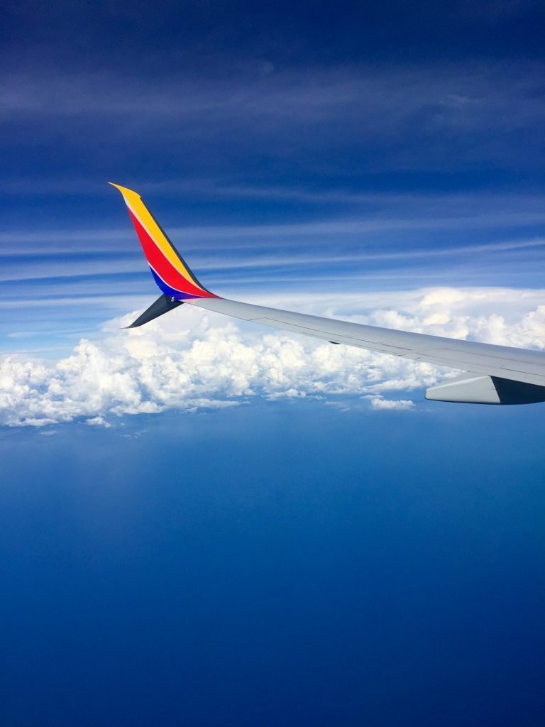 The wing of a Southwest Airlines 737 against a bright blue sky and puffy white clouds.