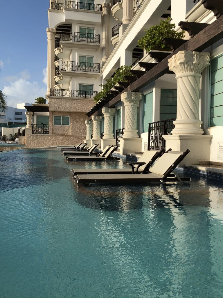 View of lounge chairs in the water in the pool area at the Hyatt Zilara Cancun