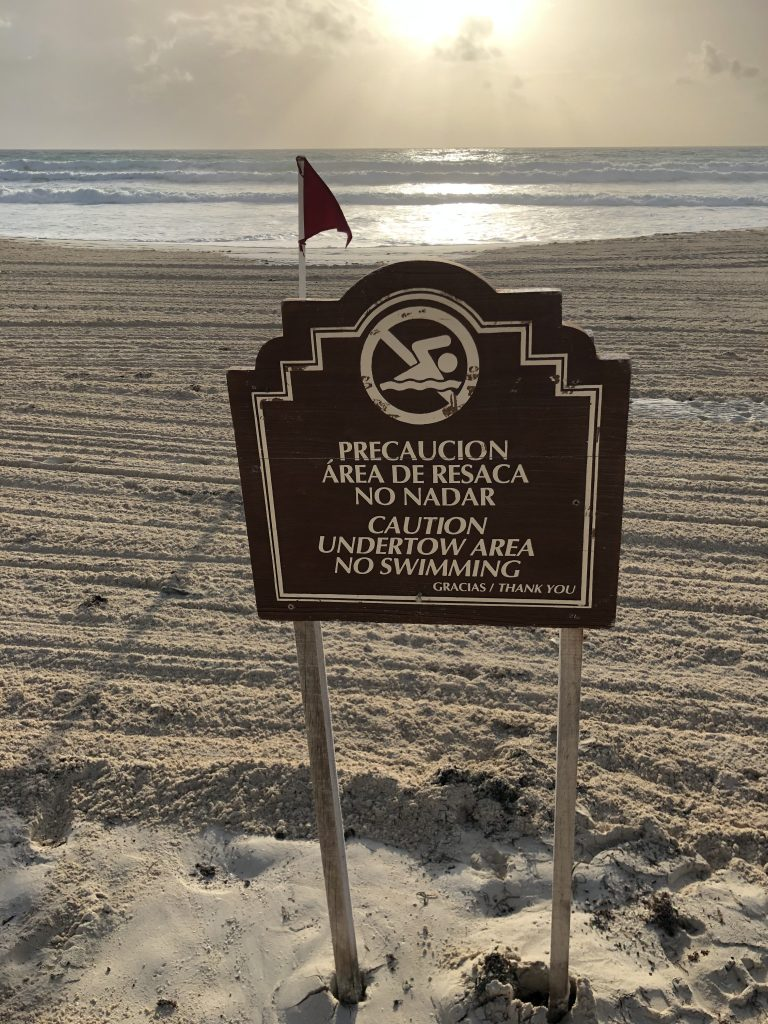 Sign on the beach in front of the Hyatt Zilara Cancun reading: Caution Undertow area. No swimming
