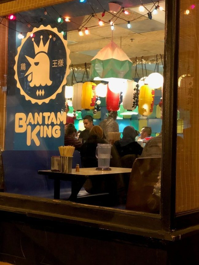 Looking through the front window, past the Bantam King logo, to patrons seated in the restaurant below lanterns. A shot of one of the best places to eat when visiting the National Mall