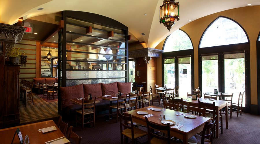 Interior shot of Lebanese Taverna in Pentagon City showing the tables, cushioned banquettes, and arched windows.