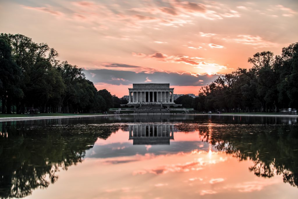 Pink clouds over the iconic Lincoln Memorial at sunset are beautifully mirrored in the reflecting pool. Despite the serene setting, good eating options can be found nearby.