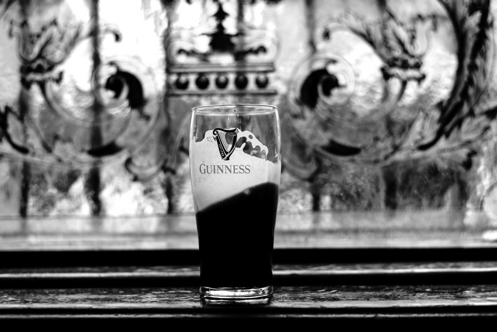 A black and white photo of a half full glass of foaming Guinness sitting on a wooden bar
