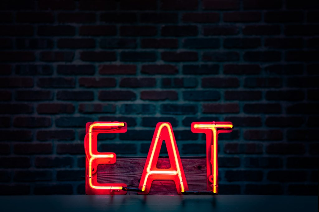 "Lit restaurant sign says ""EAT"" in red capital letters"