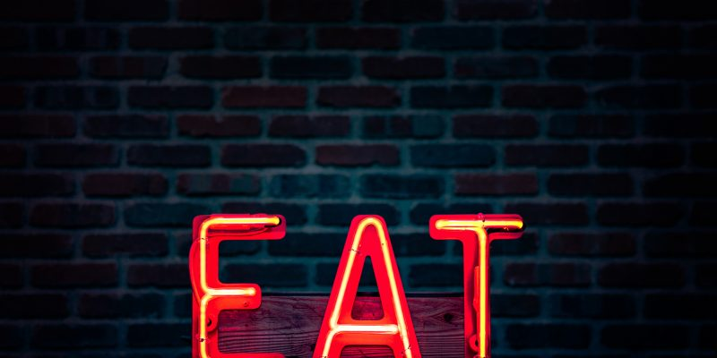 """Illuminated red sign reads """"EAT"""""""