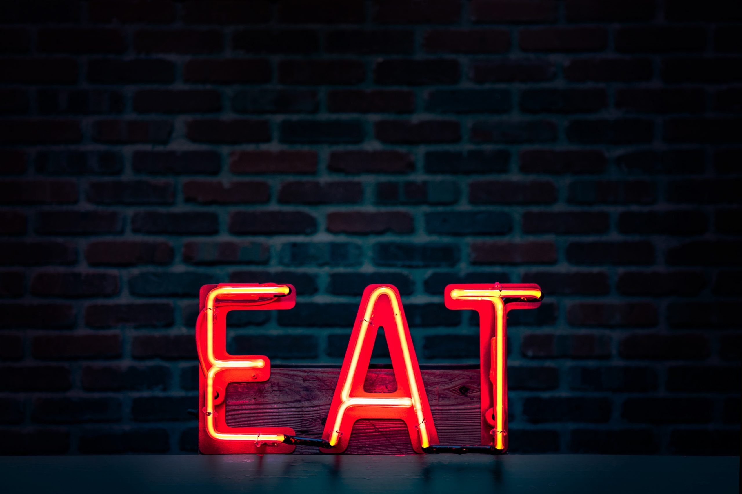 "Illuminated red sign reads ""EAT"""