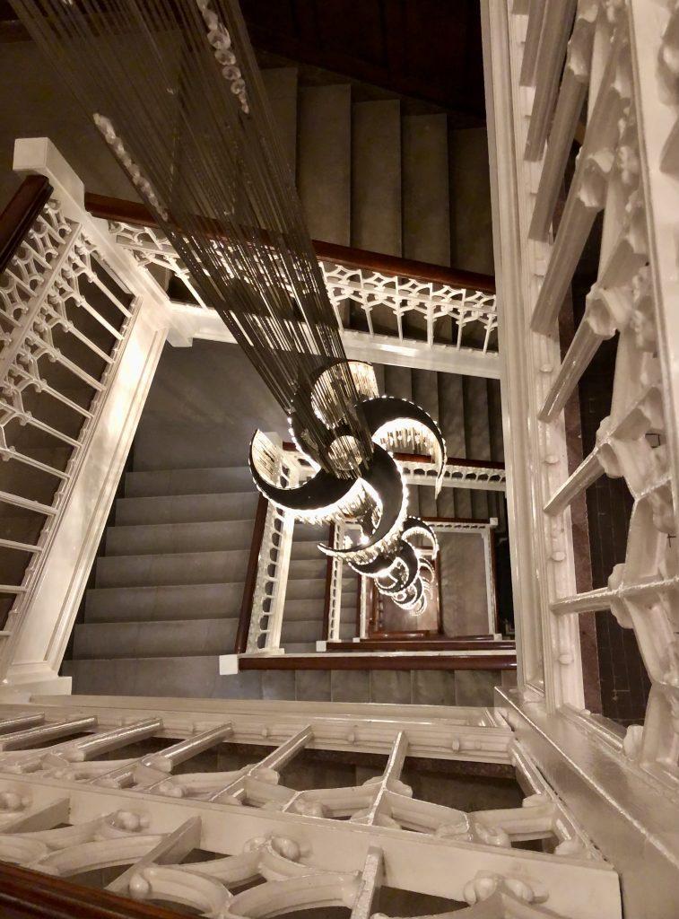 A beautiful multistory chandelier hangs in the open stairwell