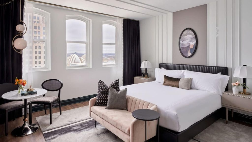 Standard room at the Hotel Kansas City, with crisp white linens, contrasting draperies, and neutral accents for a clean, modern feel